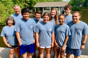 group of 9 youth and chaperones standing on a pier in matching t-shirts