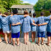 group of youth with backs to camera standing on a pier in matching t-shirts